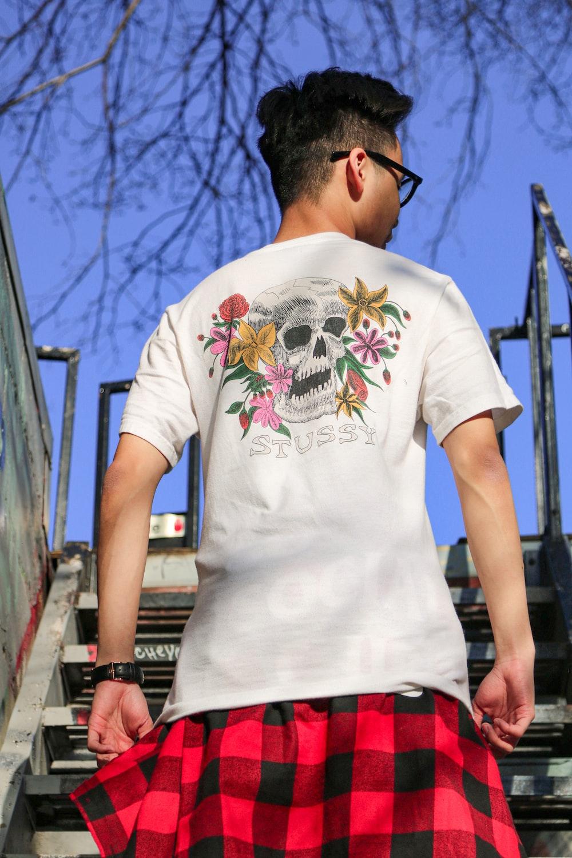 man in white crew neck t-shirt standing on bridge during daytime