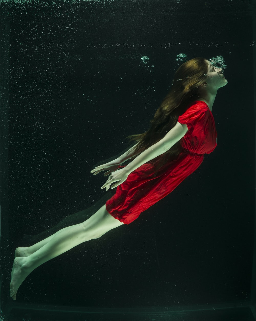 woman in red dress lying on water