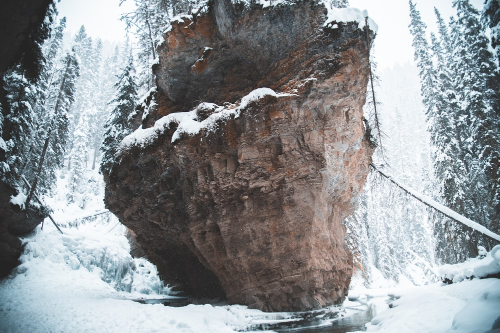 brown rock formation covered with snow during daytime