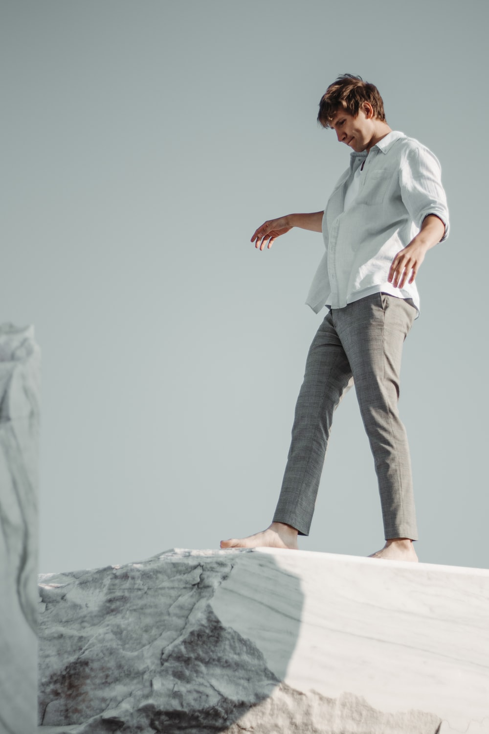 man in white button up shirt and gray denim jeans standing on gray rock