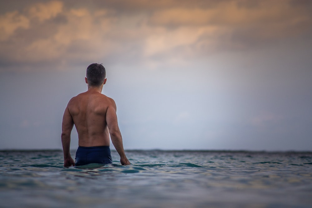 topless man in blue shorts standing on water during daytime