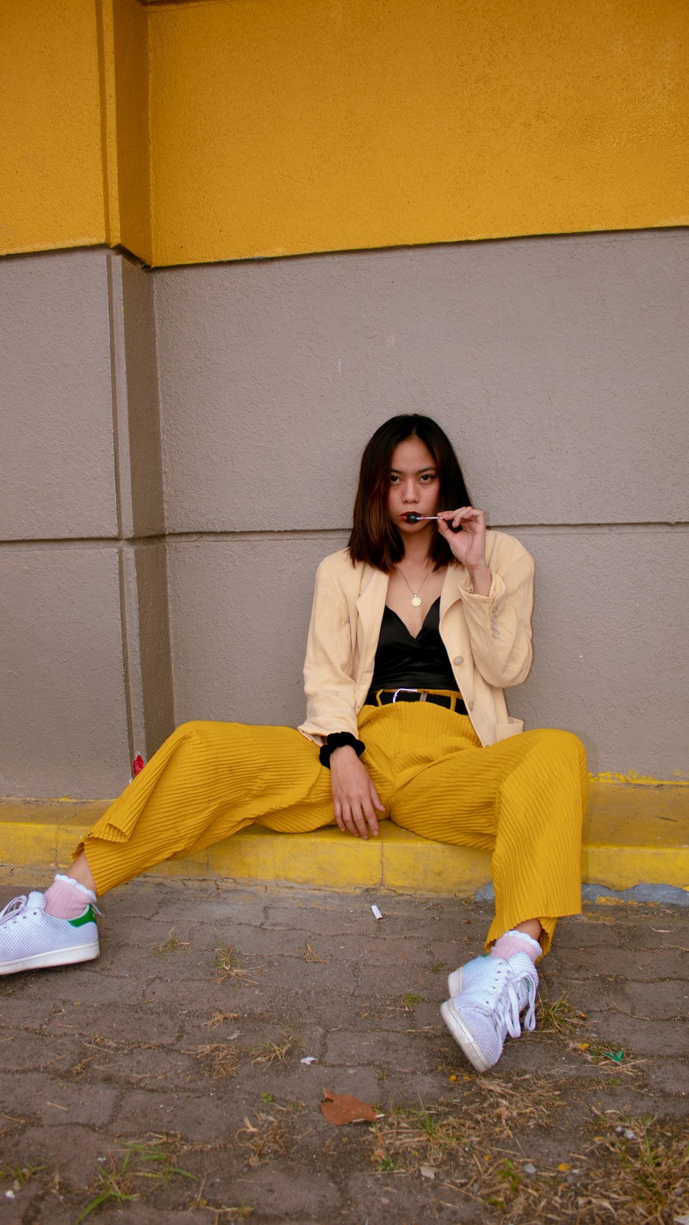 woman in yellow pants sitting on concrete stairs