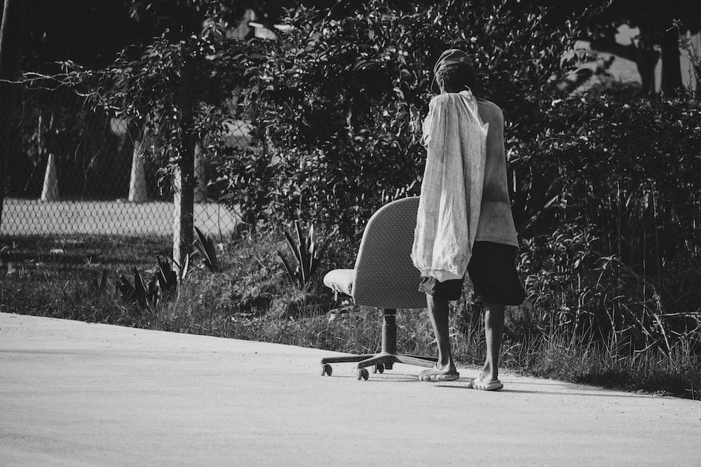woman in white coat walking on road