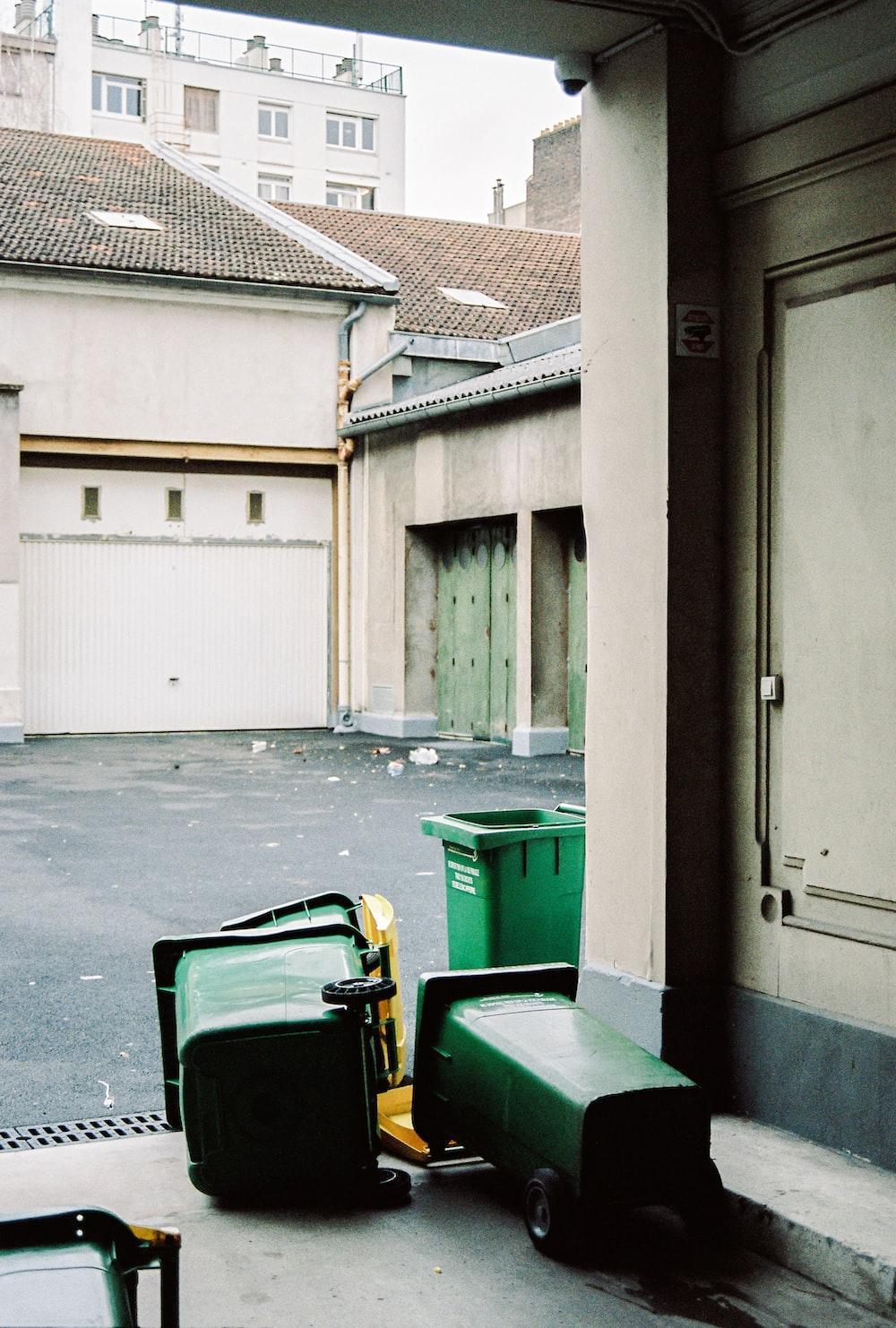 green trash bin beside white wooden door
