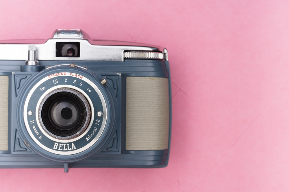black and silver camera on pink textile