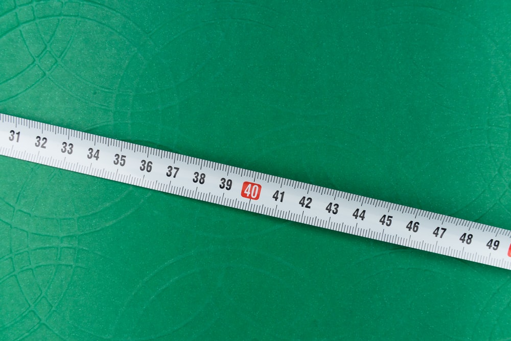 white ruler on green textile