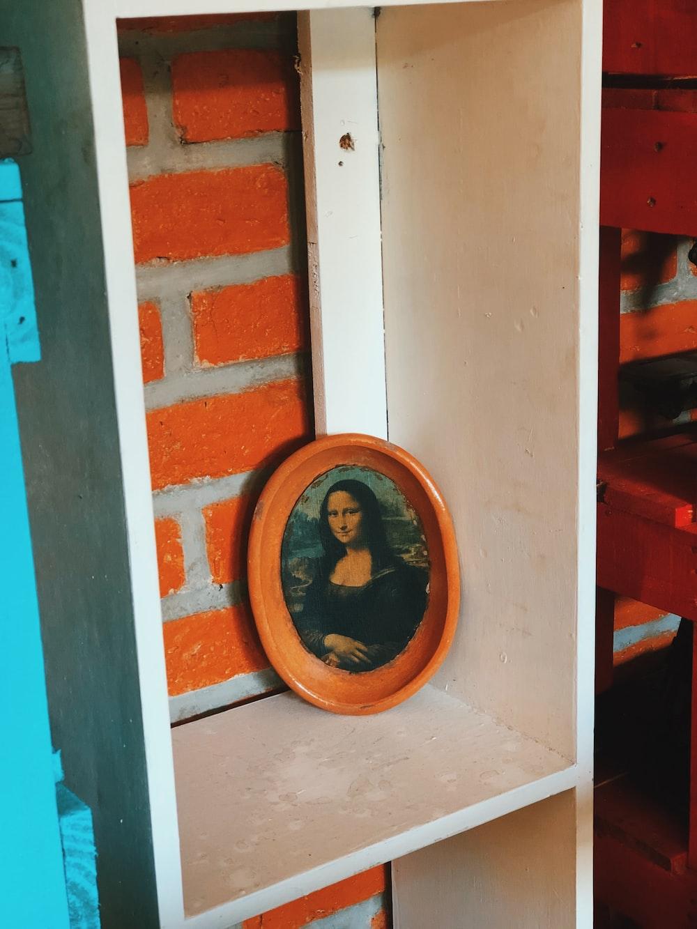 brown wooden round frame on brown wooden shelf