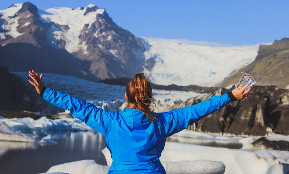 woman in blue jacket standing on snow covered ground during daytime