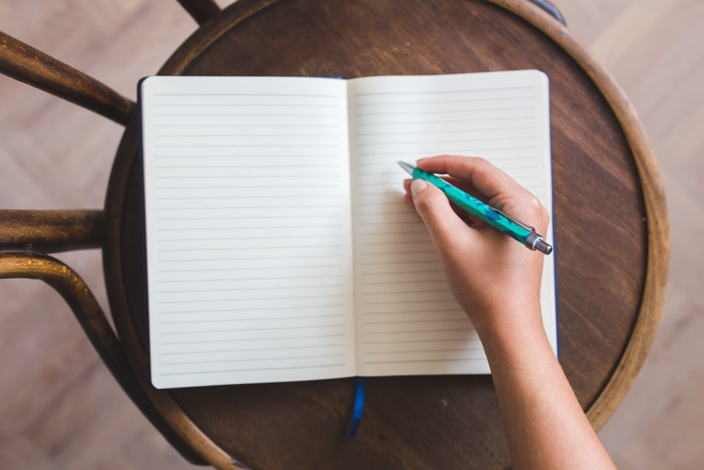 person holding blue click pen on white notebook