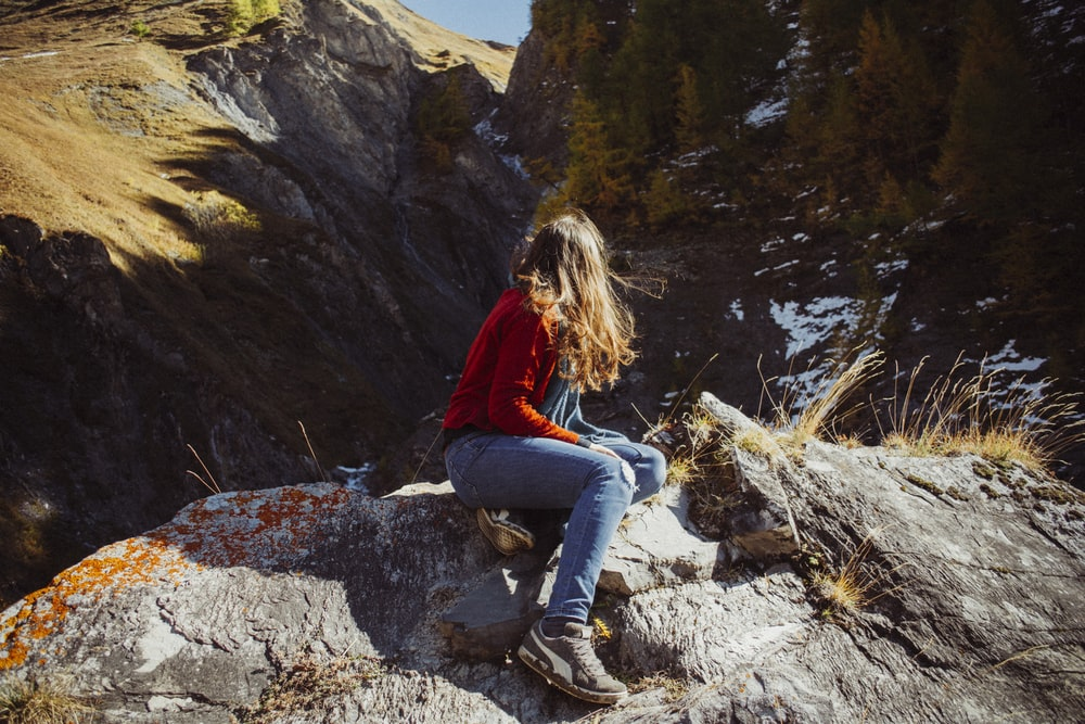 woman in red jacket and blue denim jeans sitting on rock near river during daytime