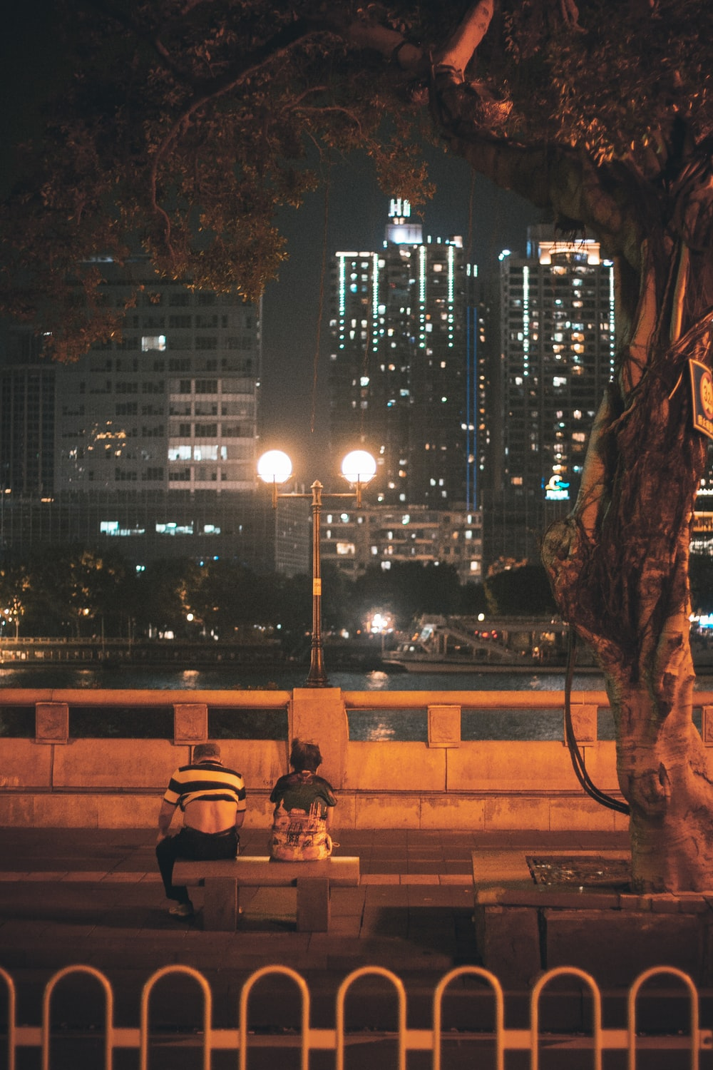 2 person sitting on bench near city buildings during night time