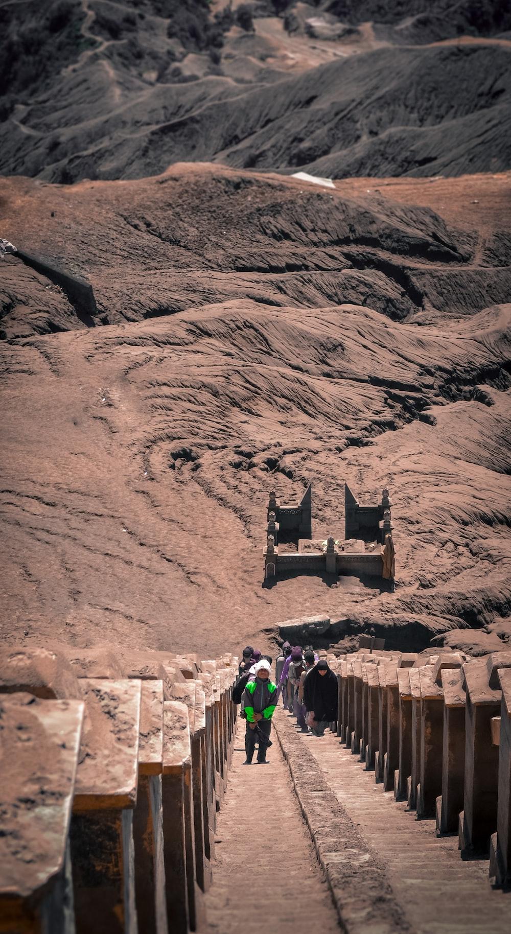 people walking on brown rock formation during daytime
