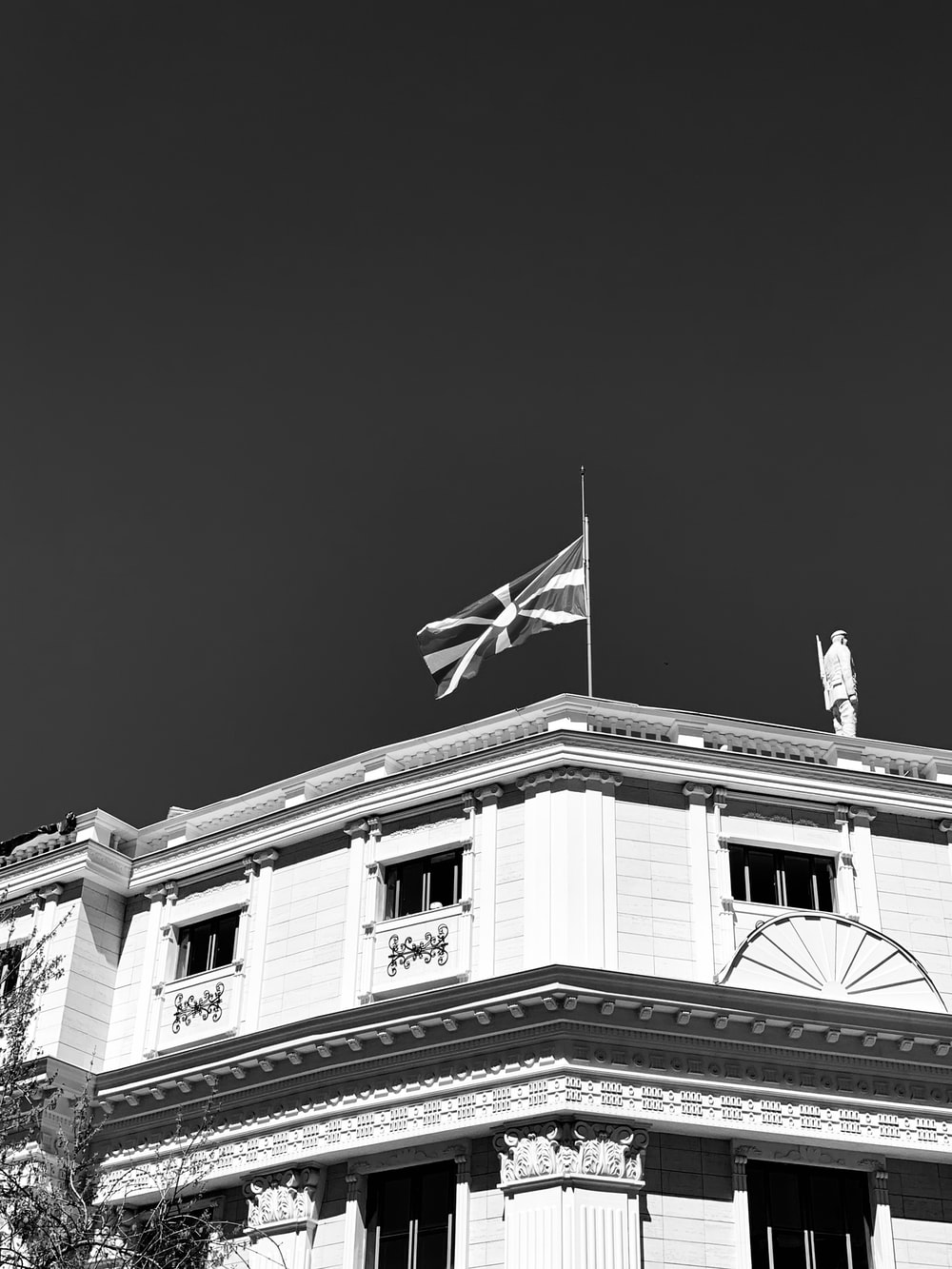 grayscale photo of building with flag on top