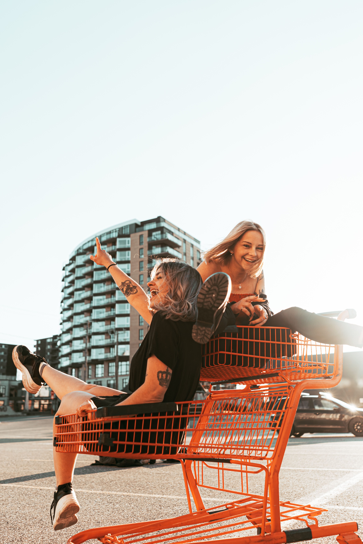 woman in black dress holding shopping cart