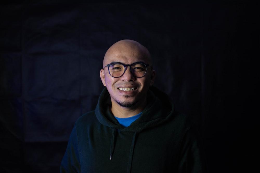 man in black hoodie wearing black framed eyeglasses