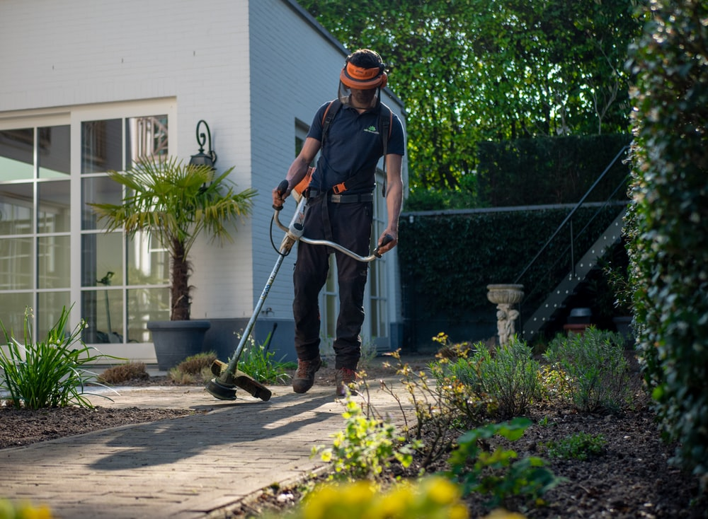man in black t-shirt and blue denim jeans holding shovel