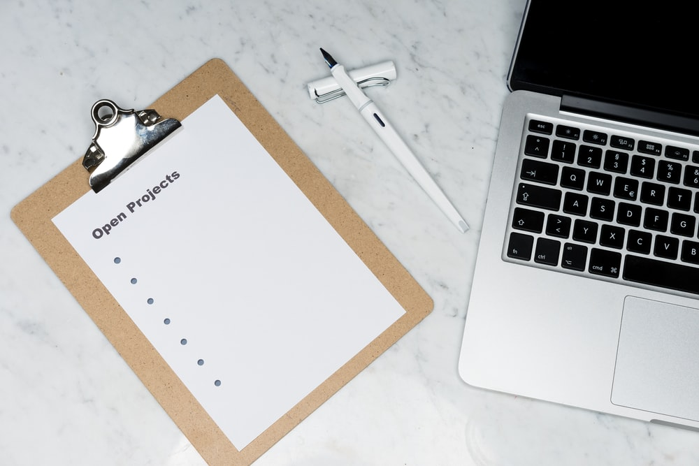 white printer paper beside silver laptop computer