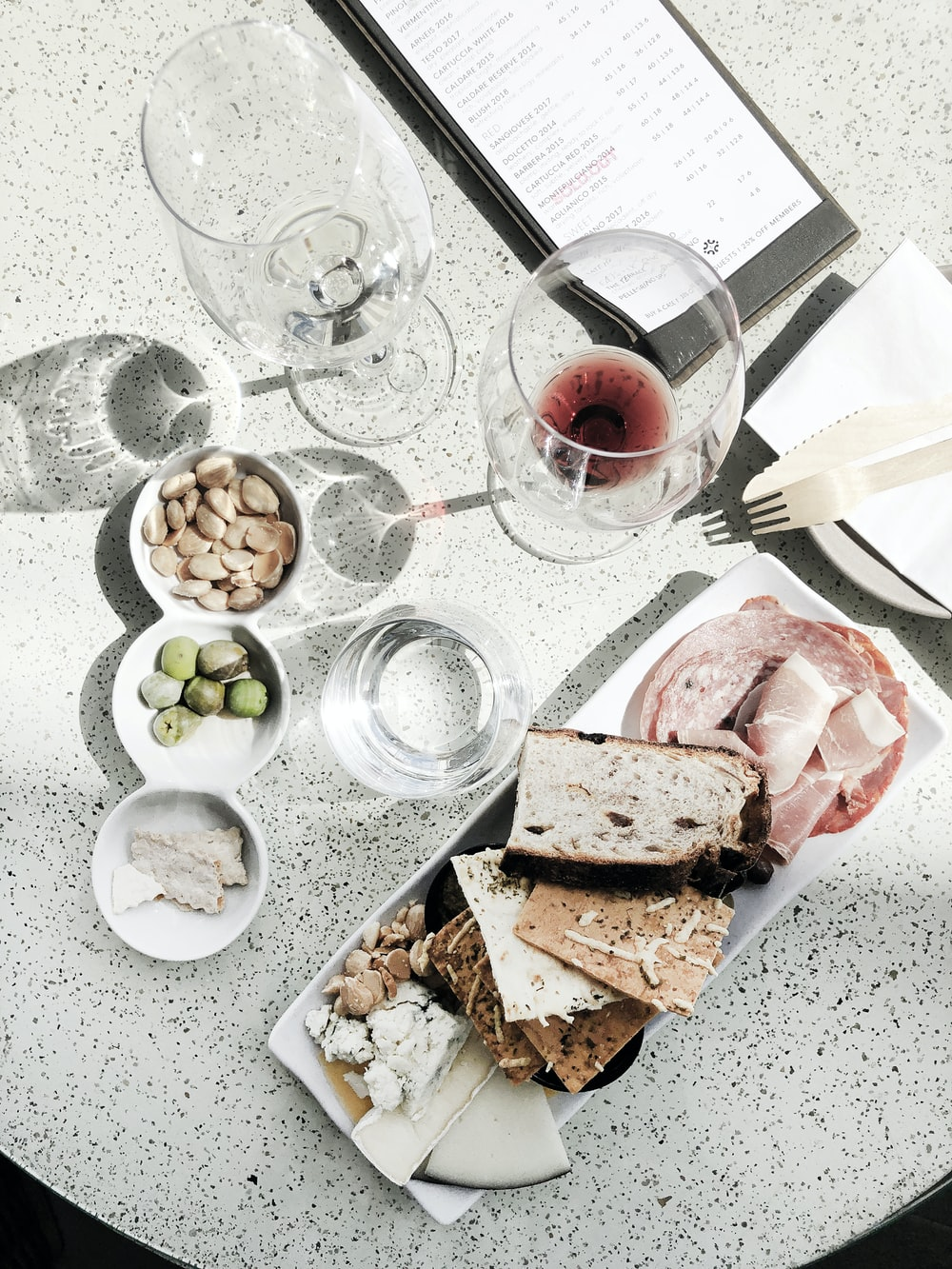 sliced bread on white ceramic plate beside clear wine glass