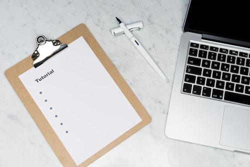 white paper on brown folder beside silver key