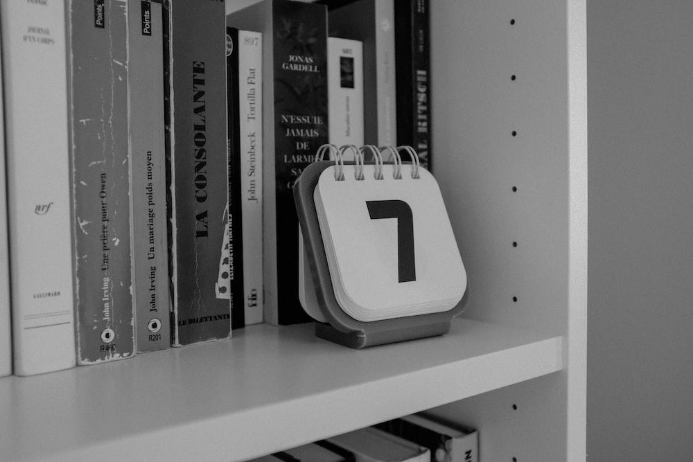 white and black plastic case on white wooden shelf