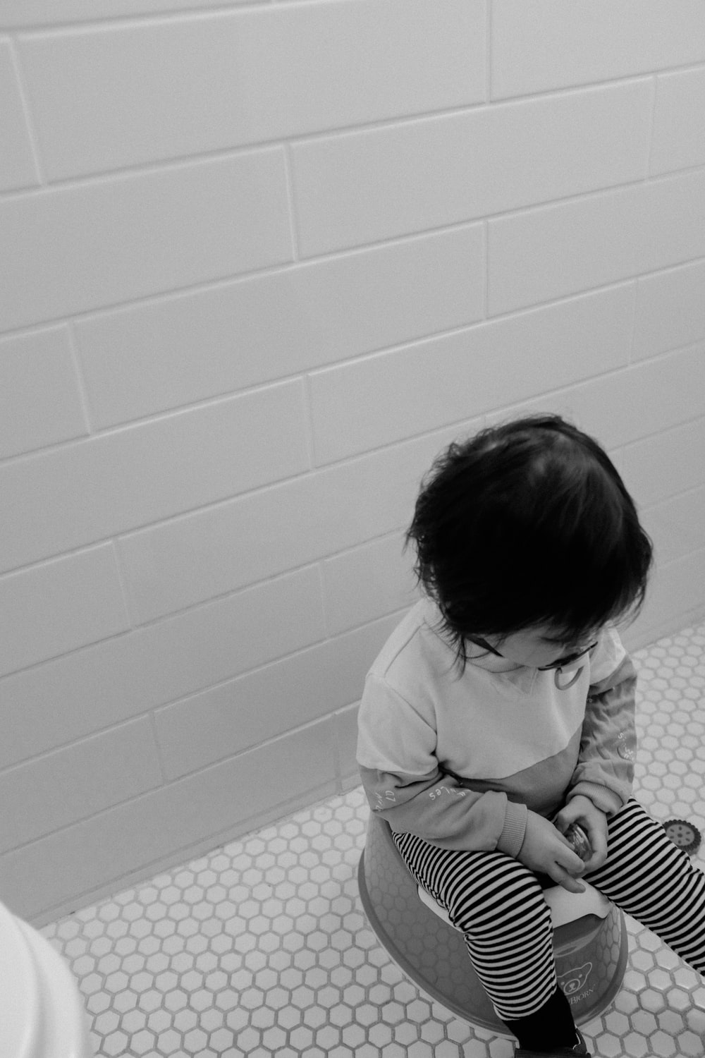 grayscale photo of child in white long sleeve shirt sitting on floor