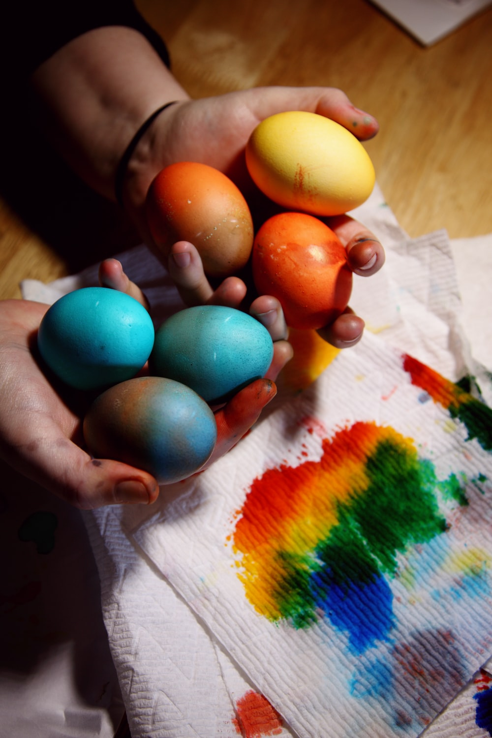 person holding blue and yellow egg