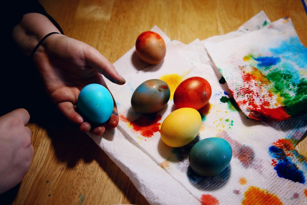 person holding red yellow and blue egg