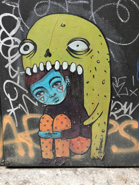 Bronik Street art in Barcelona El Born. A green monster eating a blue little girl or boy.
