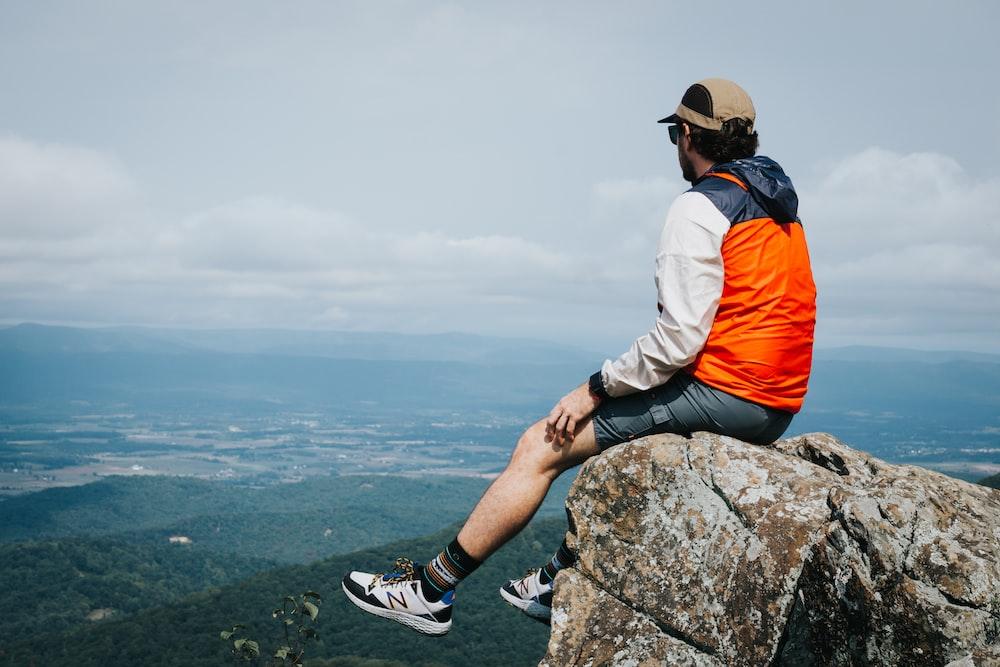 man in orange jacket sitting on rock during daytime
