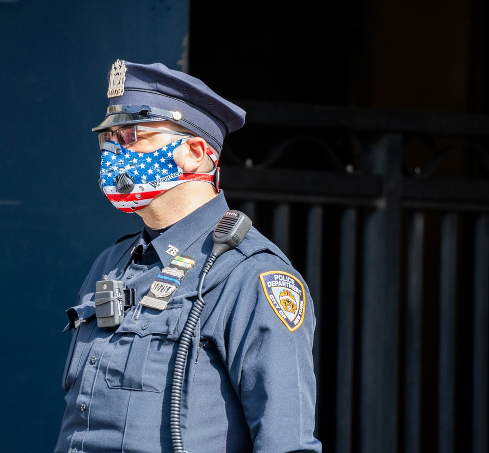 man in black and brown camouflage uniform wearing blue and white mask
