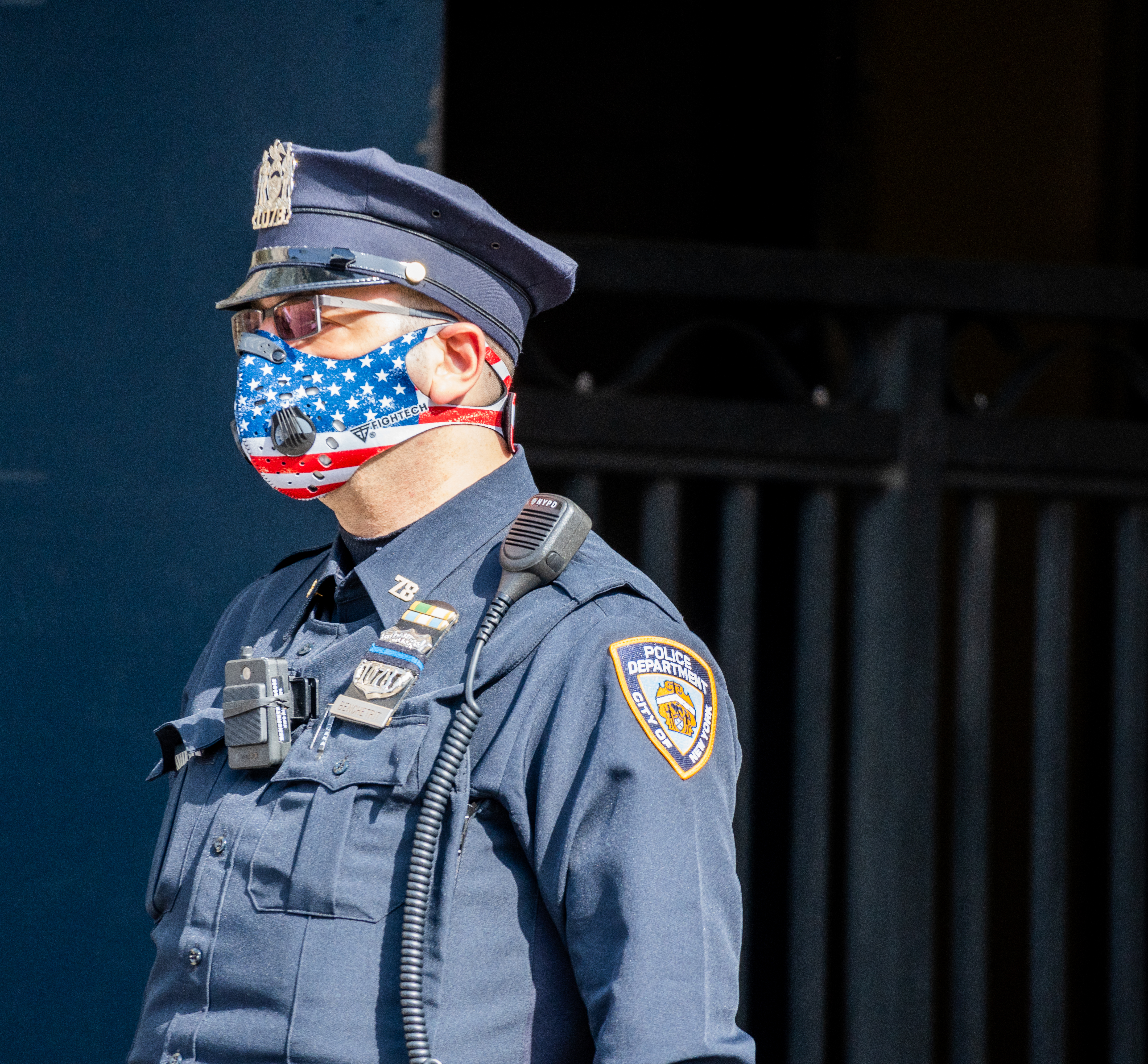 Side angle of an NYPD Officer wearing a patriotic American Flag themed N95 Ventilator Mask while on duty in New York City during the difficult period of Coronavirus policing.