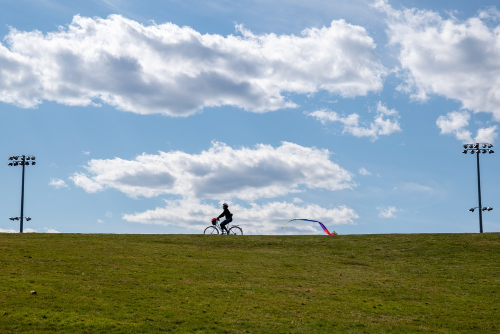 2 men riding on bicycle on green grass field under white clouds and blue sky during