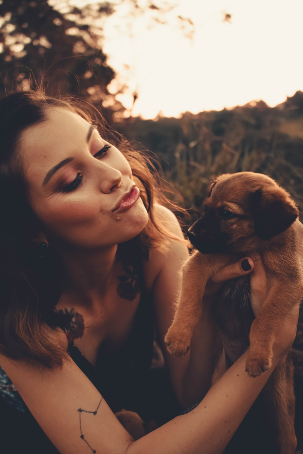 woman holding brown short coated puppy during daytime