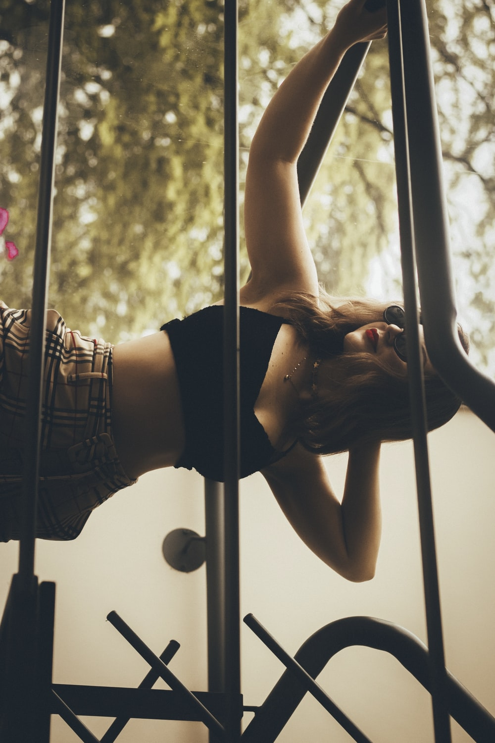 woman in black sports bra and brown shorts climbing on ladder