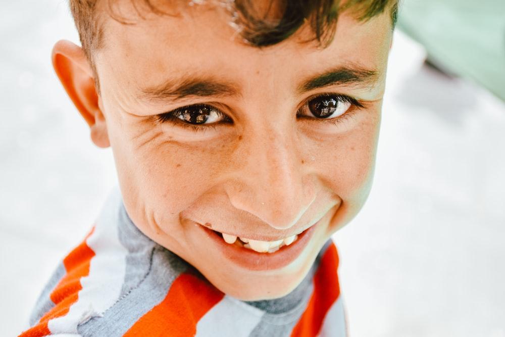 boy in white and orange collared shirt