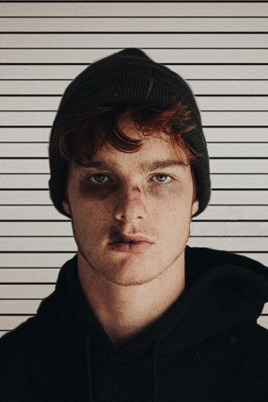 man in black knit cap and black hoodie