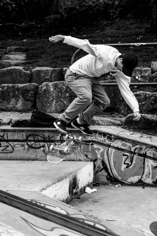 man in white t-shirt and black pants doing skateboard stunts on black metal railings