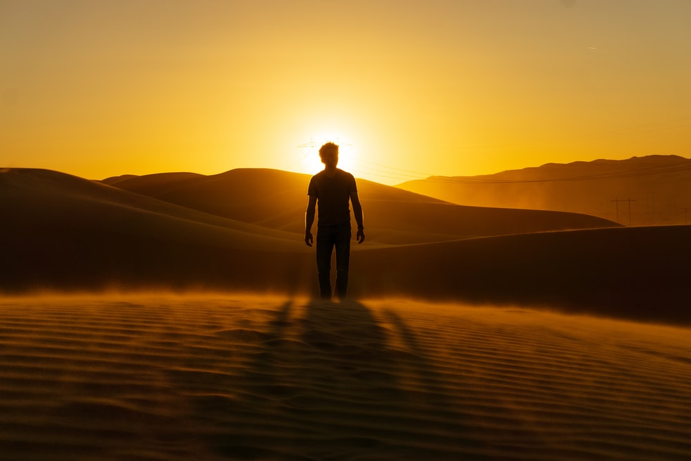 man in black jacket standing on brown sand during sunset
