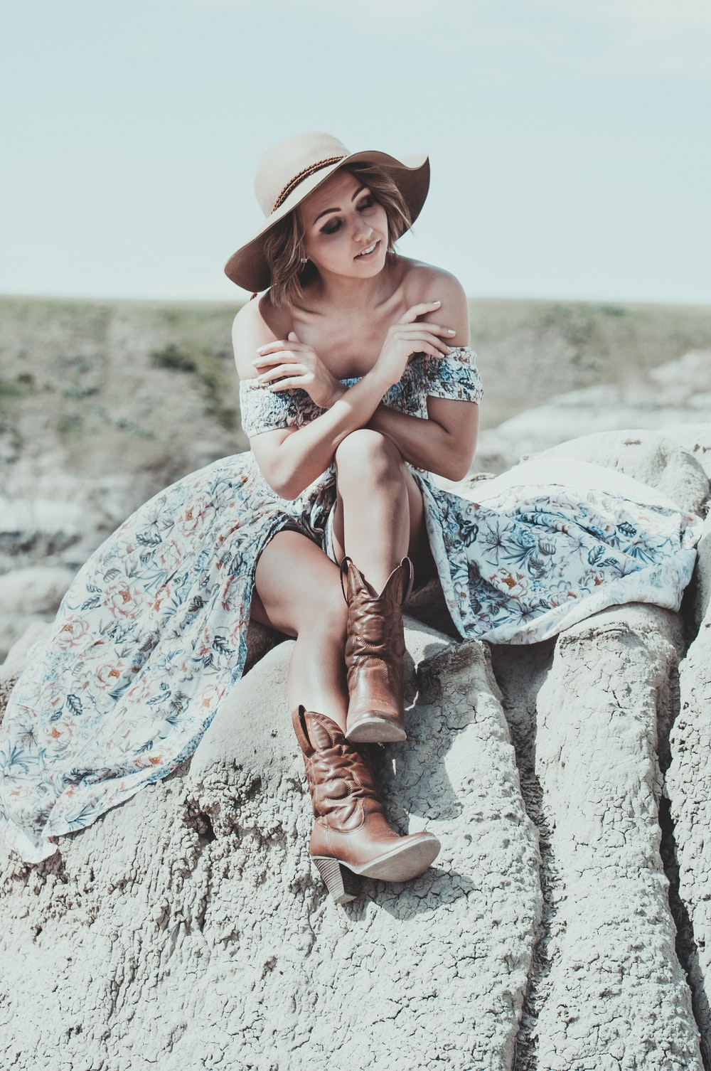 woman in blue and white floral dress wearing brown cowboy boots sitting on gray rock during