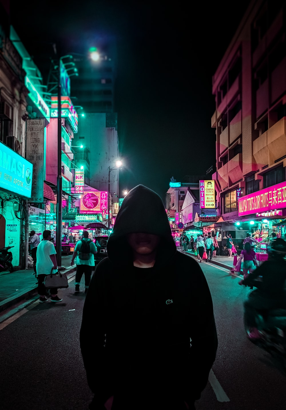 man in black hoodie walking on street during night time