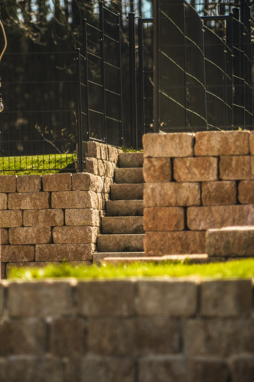 brown brick wall near green grass during daytime