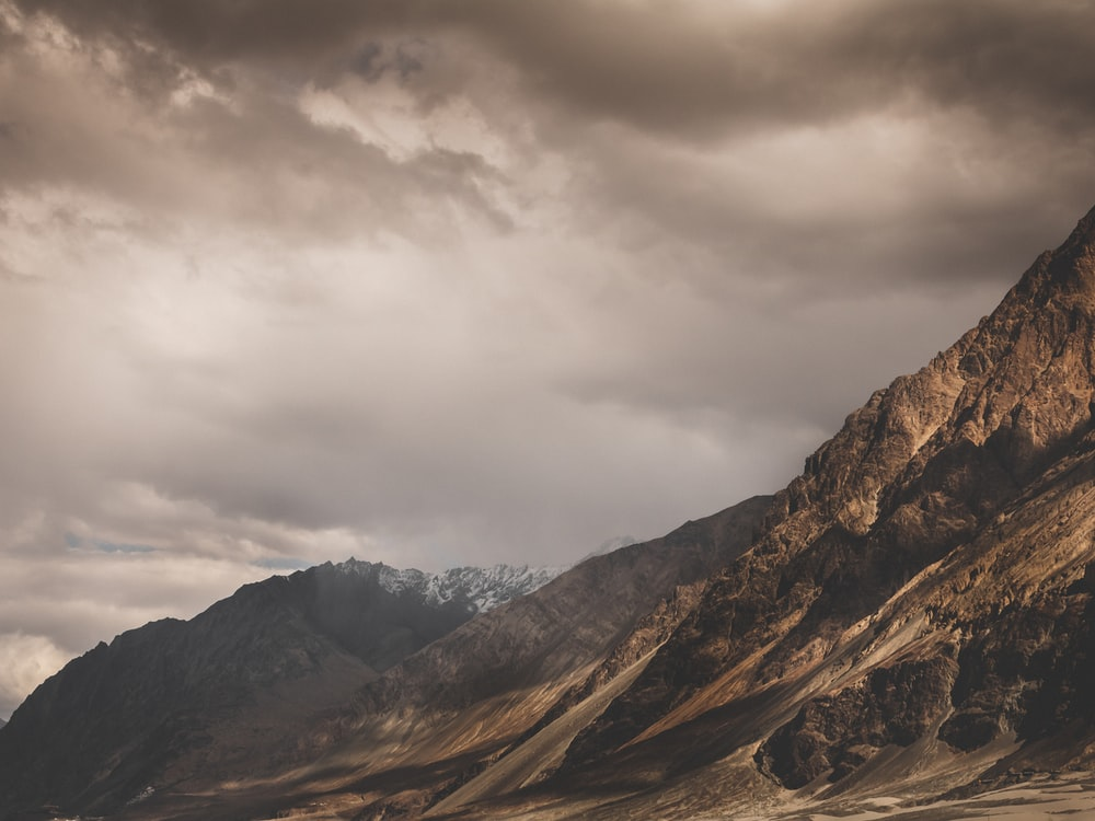 brown and gray mountains under gray clouds