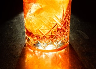 clear drinking glass with orange liquid and ice