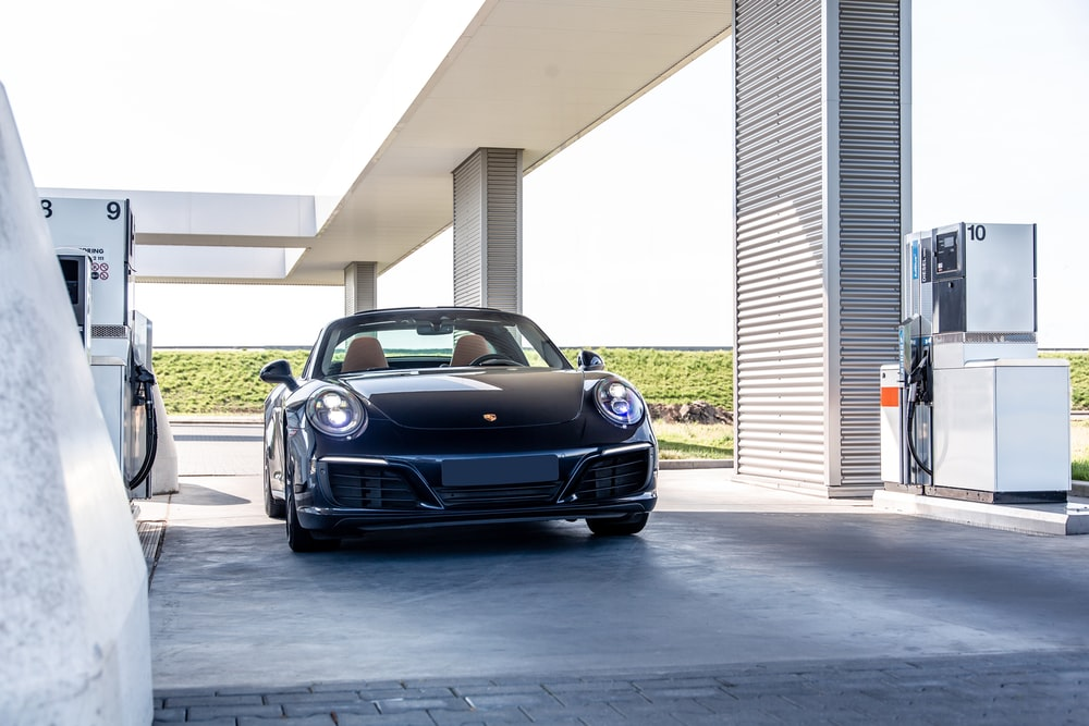 black porsche 911 parked in front of white building