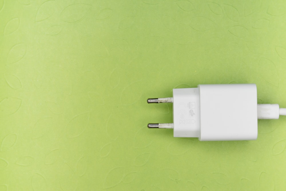 white adapter on green surface