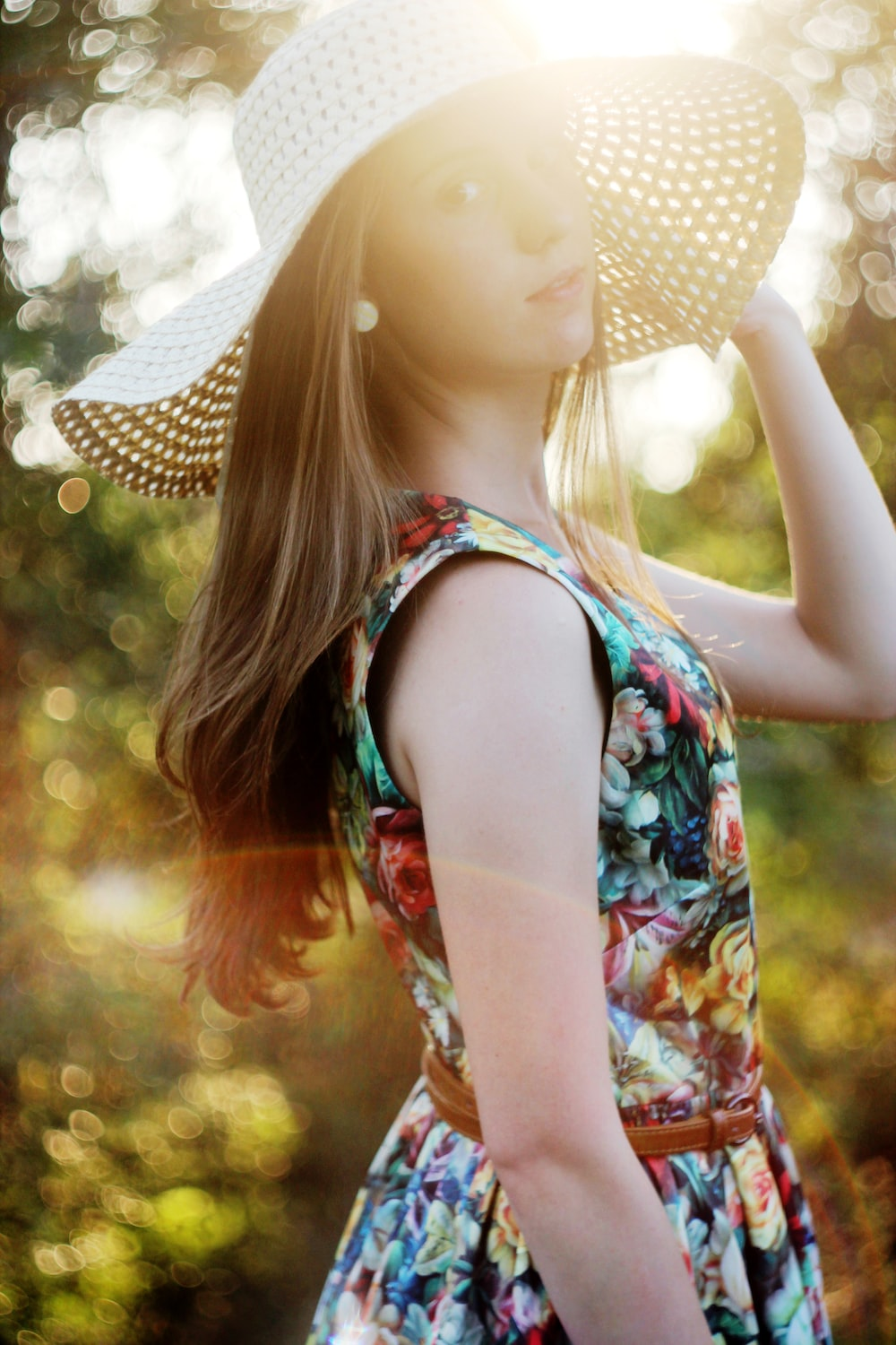 woman in white and blue floral tank top wearing white and black polka dot sun hat