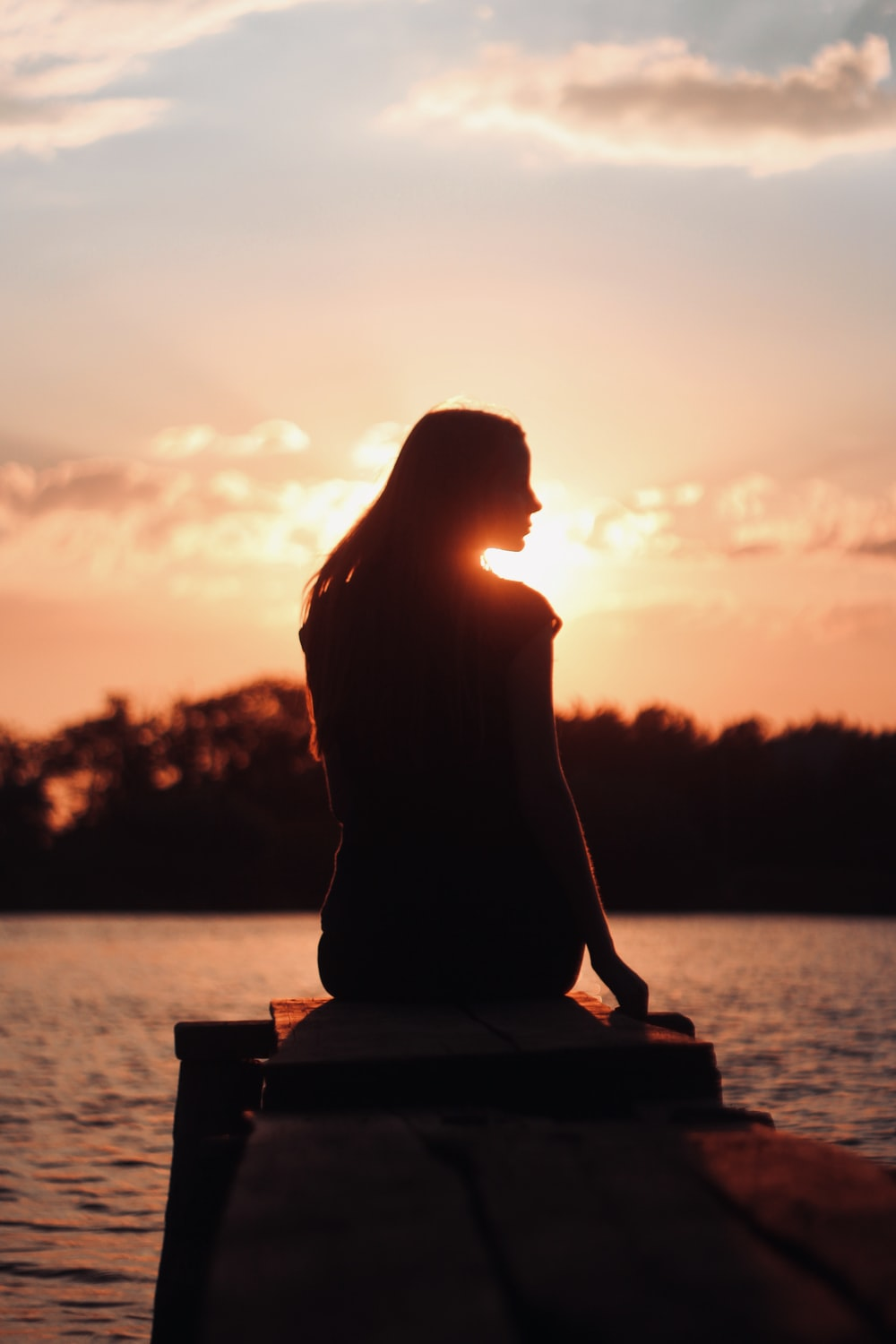 silhouette of woman sitting on brown wooden bench during sunset