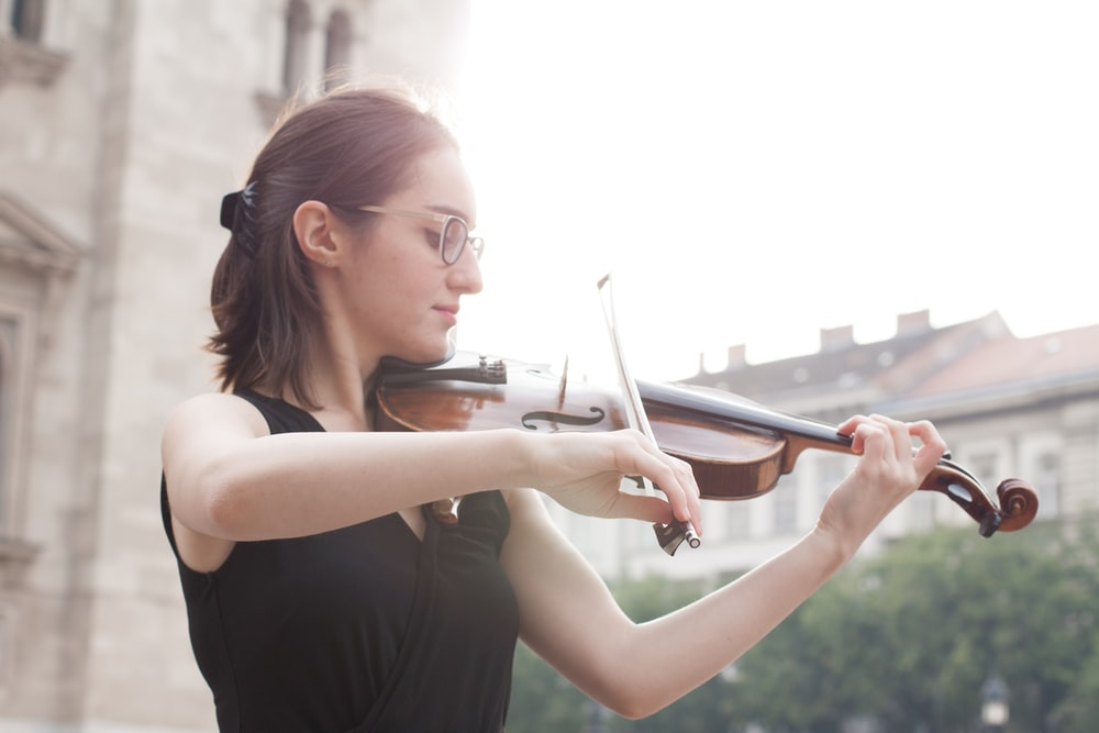 woman in black tank top playing violin during daytime