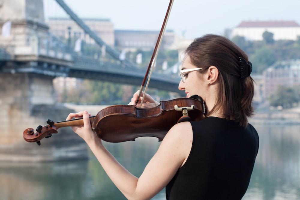 woman in black tank top playing violin