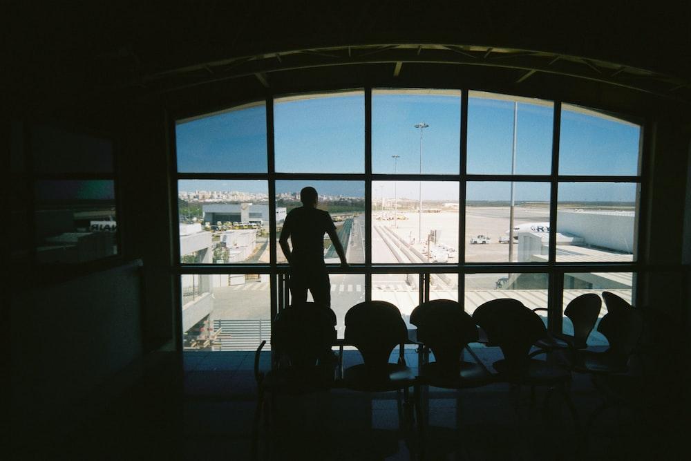 silhouette of man standing near glass window